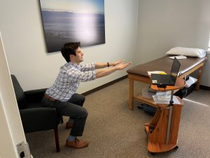 Male therapist in telehealth physical therapy session